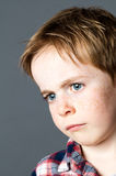 Primer, niño joven decepcionado con los ojos azules tristes y pecas imagen de archivo