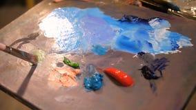 Primer Paleta con las pinturas multicoloras El artista mezcla color 4K MES lento almacen de video