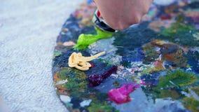 Primer, paleta del arte El artista exprime un poco de pintura verde de un tubo hay un proceso creativo pinturas del artista adent metrajes