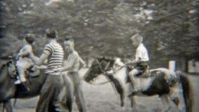 1949: Primer paseo del caballo del bebé con el papá que se sostiene para la seguridad NEWARK, NEW JERSEY almacen de video