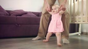 Primer paso en vida El bebé hermoso se levanta con la ayuda del padre almacen de video