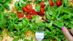 Primer, pizza jugosa, caliente grande con los tomates de los verdes, del arugula y de cereza las manos femeninas cortaron la pizz almacen de video