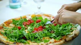 Primer, pizza jugosa, caliente grande con los tomates de los verdes, del arugula y de cereza las manos femeninas cortaron la pizz almacen de metraje de vídeo