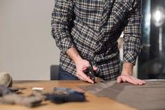 Primer que corta la tela marrón de las lanas de la tela escocesa la línea modelo Funcionamiento del hombre joven como sastre y us Imágenes de archivo libres de regalías