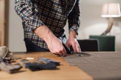 Primer que corta la tela marrón de las lanas de la tela escocesa la línea modelo Funcionamiento del hombre joven como sastre y us Imagen de archivo libre de regalías