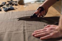 Primer que corta la tela marrón de las lanas de la tela escocesa la línea modelo Funcionamiento del hombre joven como sastre y us Fotografía de archivo libre de regalías