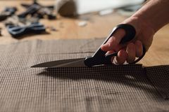 Primer que corta la tela marrón de las lanas de la tela escocesa la línea modelo Funcionamiento del hombre joven como sastre y us Fotografía de archivo