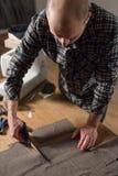 Primer que corta la tela marrón de las lanas de la tela escocesa la línea modelo Funcionamiento del hombre joven como sastre y us Imagenes de archivo