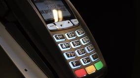 Primer que empuja el botón y la paga manualmente con la tarjeta de crédito sin contacto en la tienda almacen de metraje de vídeo