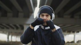 Primer que sigue el tiro del boxeador juguetón del hombre en los auriculares que hacen ejercicio del boxeo en la ubicación urbana metrajes
