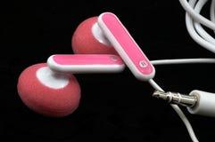 Primer rosado de Earbuds, macro, en negro Imagen de archivo libre de regalías