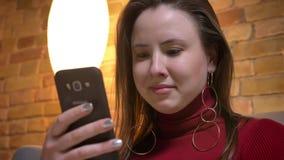 Primer shoo9t del caucásico gordo bonito joven femenino usando el teléfono dentro en un apartamento acogedor metrajes