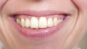 primer sonriente de los dientes y de los labios de la muchacha Primer de los labios del beso Sonrisa hermosa de una mujer joven almacen de metraje de vídeo