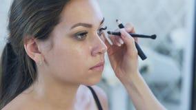 Primer Steadicam El modelo moreno se está sentando en un estudio de la belleza, ella está haciendo maquillaje del ojo de un profe almacen de video