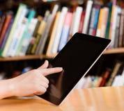 Primer stedent usando la tableta en biblioteca Imágenes de archivo libres de regalías