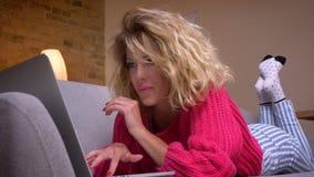 Primer tirado de ama de casa rubia en el suéter rosado que miente en el estómago en el sofá que practica surf en ordenador portát metrajes