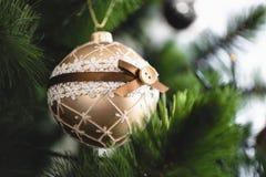 Primer tirado de bola de oro en el árbol de navidad Fotos de archivo libres de regalías