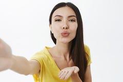 Primer tirado de hembra apuesta enérgica con el pelo oscuro que tira de la mano hacia cámara como si sostenga smartphone fotos de archivo libres de regalías
