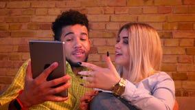 Primer tirado de individuo africano y de la muchacha caucásica que miran en la tableta y que discuten con uno a alegre en casa almacen de video