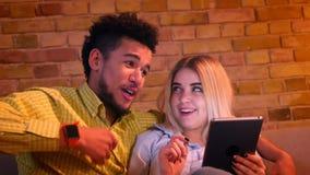 Primer tirado de individuo africano y de la muchacha caucásica que miran junto en la tableta y que discuten alegre en casa almacen de video