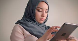 Primer tirado de la empresaria musulm?n en hijab que mira en la tableta atento que es sumergida en el trabajo en butaca almacen de video
