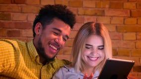 Primer tirado de la muchacha caucásica que mecanografía en la tableta y el individuo africano que miran en ella atento en casa almacen de metraje de vídeo