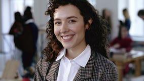 Primer tirado de la mujer de negocios joven europea feliz del empresario que sonríe alegre con el pelo rizado en la oficina moder almacen de video