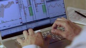 Primer tirado de la pantalla de ordenador del ordenador portátil Hombre que prepara los diagramas para la reunión de negocios almacen de metraje de vídeo