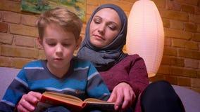 Primer tirado de pequeño muchacho concentrado y de su madre musulmán en learnin del hijab cómo leer ser atento en casa almacen de metraje de vídeo