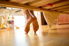 Primer tirado de pies femeninos debajo de cama Fotografía de archivo libre de regalías
