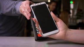 Primer tirado de smartphone femenino de los agregados de la mano al terminal que realiza el pago sin contacto acertado de los pay almacen de metraje de vídeo
