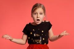 Primer tirado de una pequeña señora rubia encantadora en un vestido combinado que presenta contra un fondo rosado foto de archivo libre de regalías