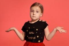 Primer tirado de una pequeña señora rubia encantadora en un vestido combinado que presenta contra un fondo rosado imagen de archivo libre de regalías