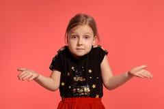Primer tirado de una pequeña señora rubia encantadora en un vestido combinado que presenta contra un fondo rosado foto de archivo
