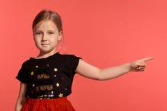 Primer tirado de una pequeña señora rubia encantadora en un vestido combinado que presenta contra un fondo rosado fotos de archivo libres de regalías