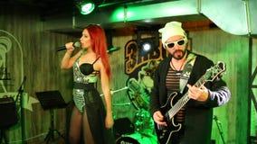 Primer tirado del funcionamiento de un cantante hermoso en el traje de plata con un guitarrista en el sombrero blanco almacen de metraje de vídeo