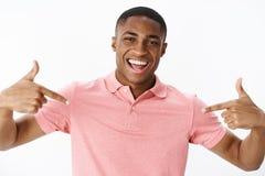Primer tirado del individuo alegre del afroamericano apuesto confiado autosatisfecho en polo rosado que señala en foto de archivo libre de regalías