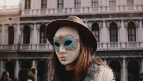 Primer tirado del turista femenino hermoso que lleva la máscara tradicional del carnaval en la cámara lenta del cuadrado de Venec almacen de video