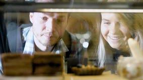 Primer a través de la exhibición de un par que mira los dulces y que elige, comiendo hacia fuera en panadería metrajes