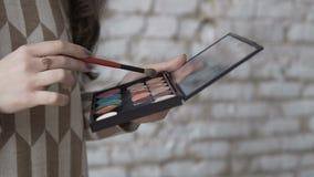 Primer Un artista de maquillaje profesional coge sombras en el cepillo Construya la mano del ` s del artista de la mujer joven co almacen de video