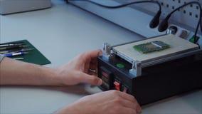 primer Un ingeniero de la reparación del técnico calienta la placa madre de una aspiradora segway almacen de metraje de vídeo