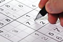 Primer un lápiz a disposición y rompecabezas Sudoku. Imagen de archivo