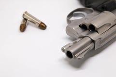 Primer una arma de mano con las balas aisladas en el fondo blanco Foto de archivo libre de regalías