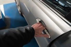 Primer una mano de los hombres en el cierre de una puerta de coche que lo abre encima - del coche del color claro imagenes de archivo