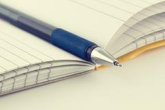 Primer una pluma azul en el cuaderno Fotos de archivo libres de regalías