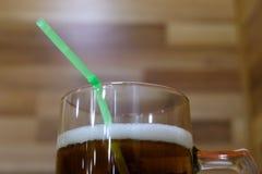 Primer Una taza de cerveza fresca con la espuma blanca y una paja verde Bebida en un partido del alcohol del verano en un café o  imágenes de archivo libres de regalías