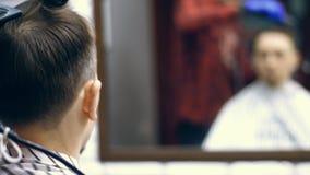 Primer, visión desde, en una tienda del baber, una peluquería de los hombres, corte del pelo de un hombre y diseñado metrajes