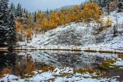 Primera caída de la nieve reflejada en el lago Sibbald Foto de archivo