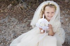 Primera muchacha de la comunión santa con el vestido, el velo y la vela Foto de archivo