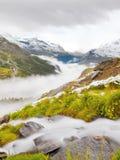 Primera nieve en la región turística de las montañas Prado verde fresco con la corriente de los rápidos Picos de las montañas de  Fotos de archivo libres de regalías